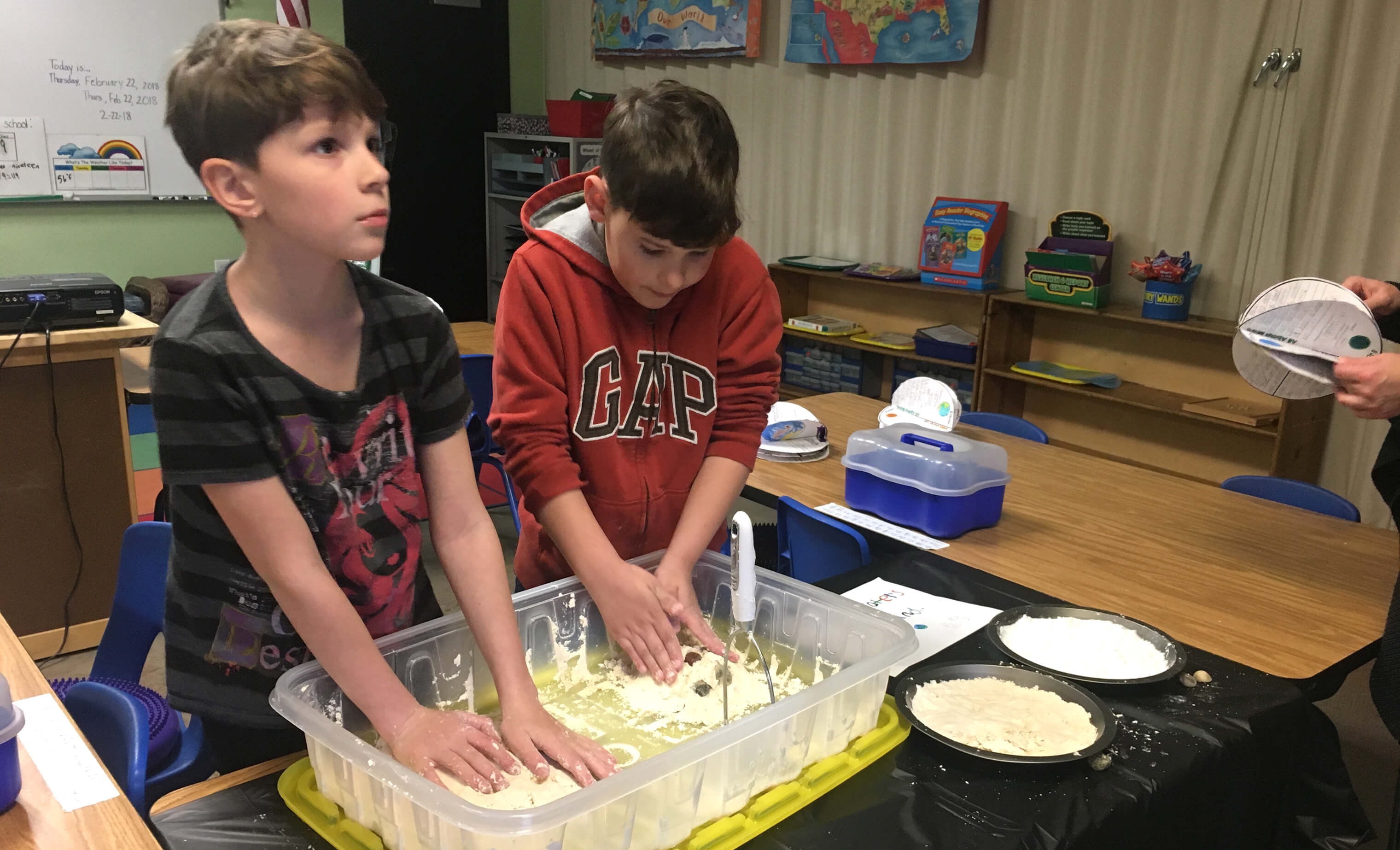 Lincoln Montessori students make craters in moon sand.