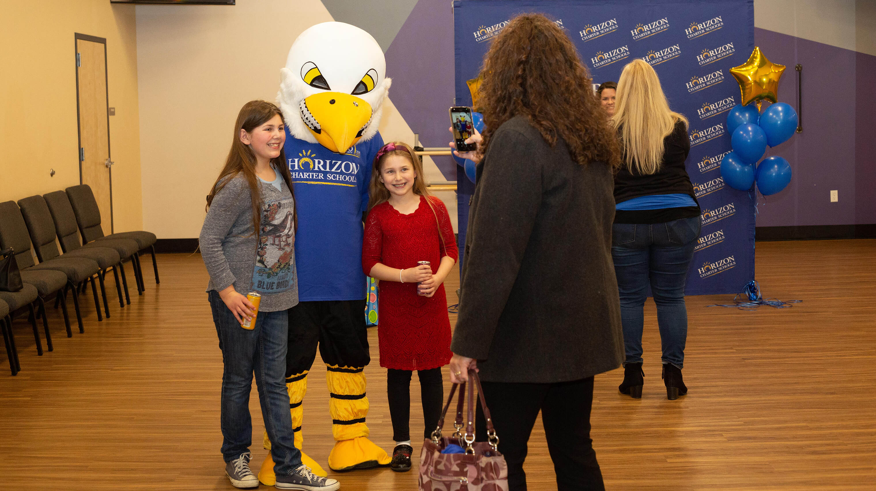 Students pose with the Horizon Charter Schools' Eagle